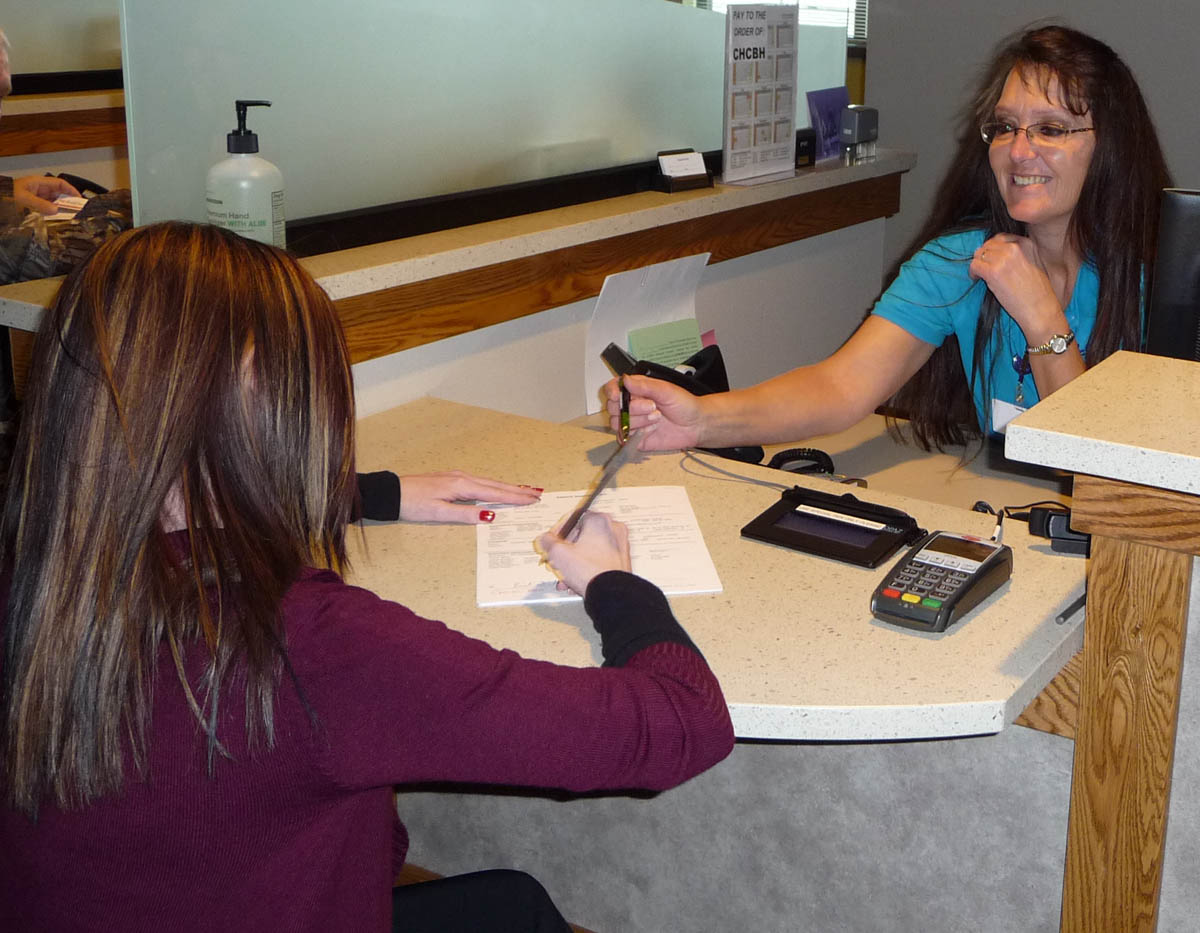 A patient filling out paperwork with the assistance of a CHCBH staff member.